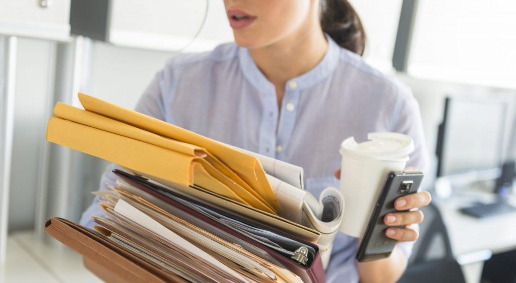 Busy woman holding folders