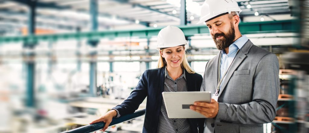 Professional male and female engineers in a factory location using a tablet to discuss business activity
