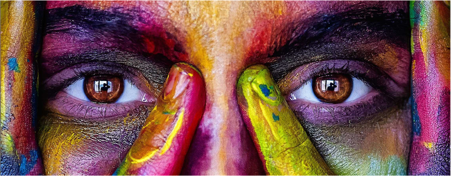 Close up image of a person s face and eyes painted with bright ink colours